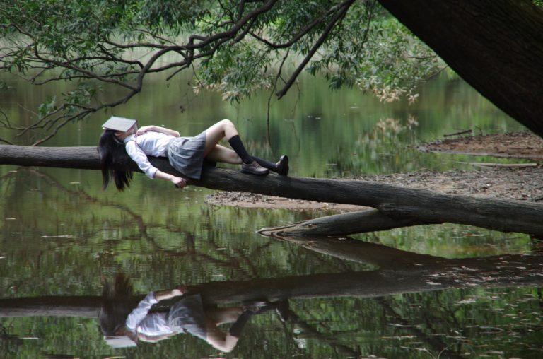 zmeczona dziewczyna na drzewie nad jeziorem